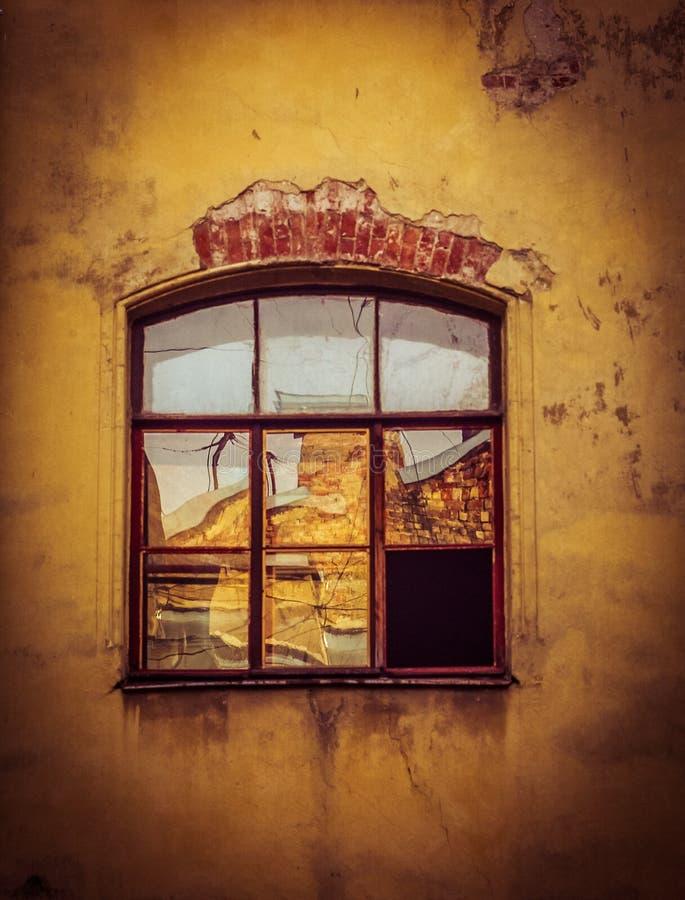 Fenster und gelbe Wand, die Reflexion im Fenster, Haus zu zerbröckeln, Fassade des Hauses stockbilder