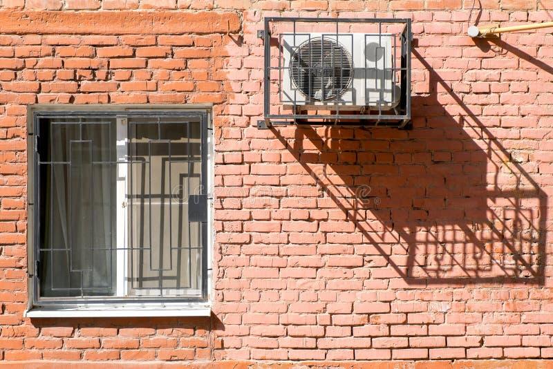 Fenster und Klimaanlage auf einer Backsteinmauer stockfotos