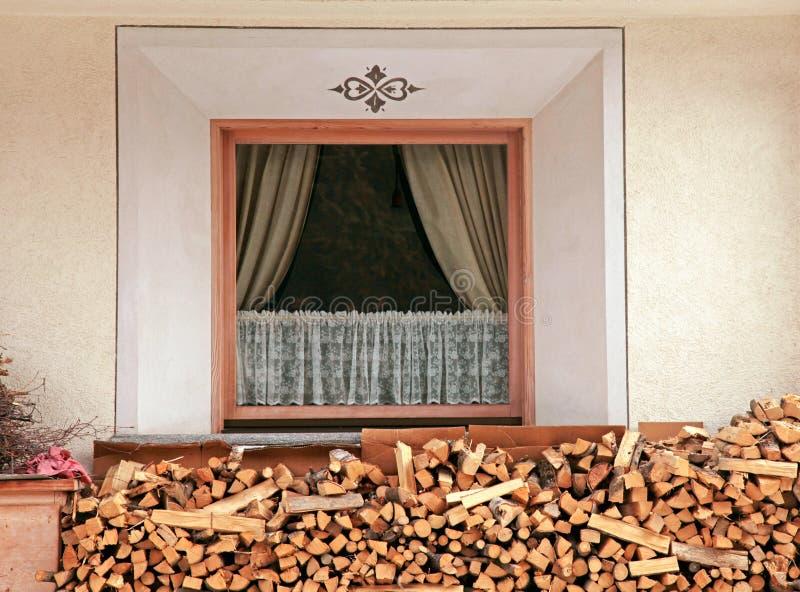 Fenster und Stapel des Brennholzes, Alpen stockbild