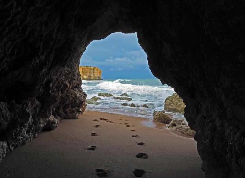 Fensteransicht über Abdrücke auf einem sandigen Strand, der zu das blaue s führt lizenzfreies stockfoto