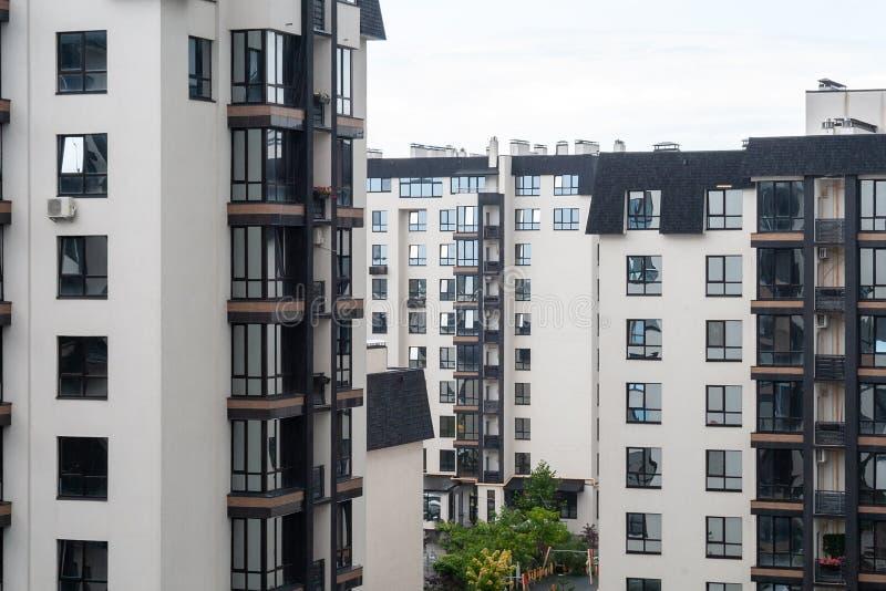 Fensteransicht von modernen weißen Wohngebäuden mit schwarzen Dächern an einem bewölkten Tag Gemütlicher Wohnkomplex lizenzfreie stockbilder