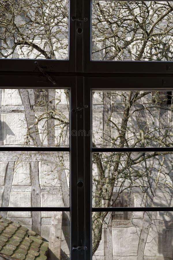 Fensterblick auf das alte Bauernhaus zurück in ein Jahrhundert lizenzfreie stockfotografie