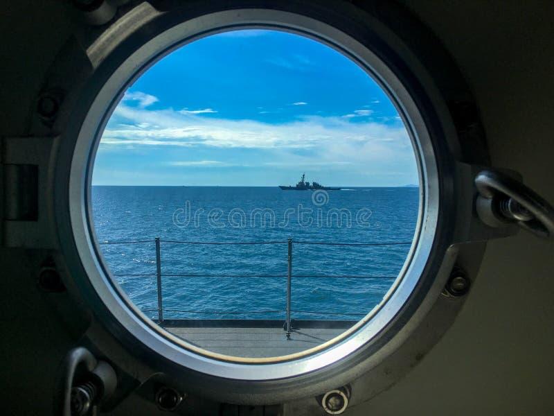 Fensterhafen des Marineschiffs mit Zerstörersegeln neben dem Beobachter ` s Schiff lizenzfreies stockbild