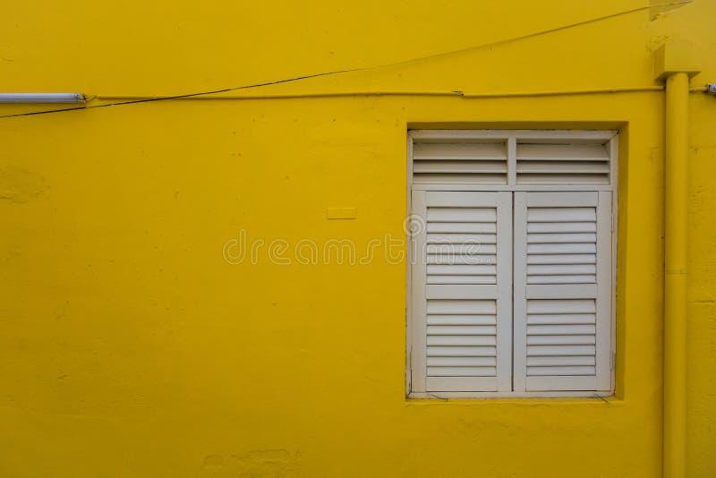 Fensterläden geschlossenes Fenster auf minimaler gelber Wand lizenzfreie stockbilder