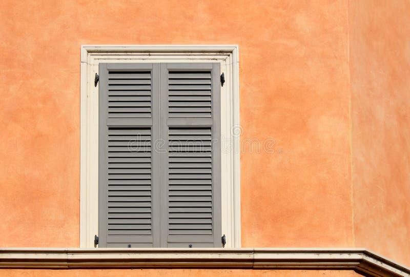 Fensterladenfenster auf einer orange Wand lizenzfreie stockbilder