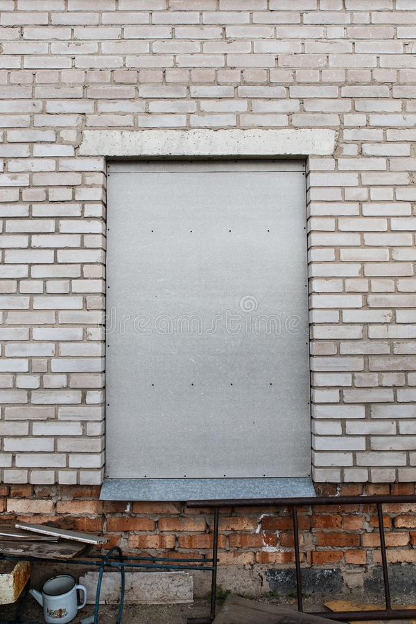 Fensters oben bricked Das Fenster wird oben mit grauem flachem Schiefer verschalt Eine graue Backsteinmauer mit einem verschalten stockfotos