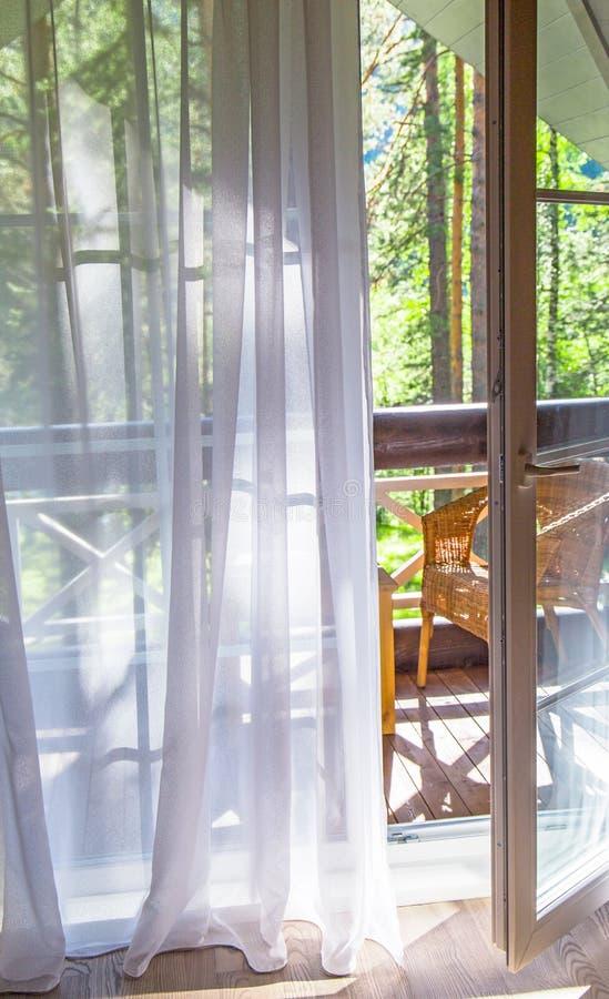 Fenstertüren öffnen sich auf einen Balkon mit Blick auf belaubte grüne Bäume nave Entspannen Sie sich Konzept berufungen stockfotografie