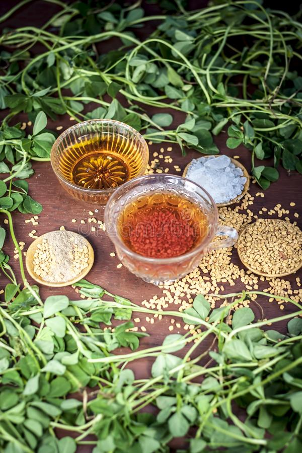 Fenugreek tea with its entire raw ingredients on wooden surface along with some raw parsley leaves. royalty free stock photography