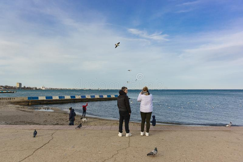 Vacationers walk on the waterfront resort town in the offseason. Weekend stock photo