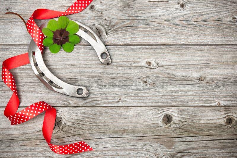 Fer à cheval, oxalide petite oseille et ruban rouge sur vieil en bois photos libres de droits