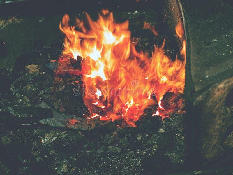 Fer de chauffage en feu pour créer le fer à cheval sur l'abvil photo stock