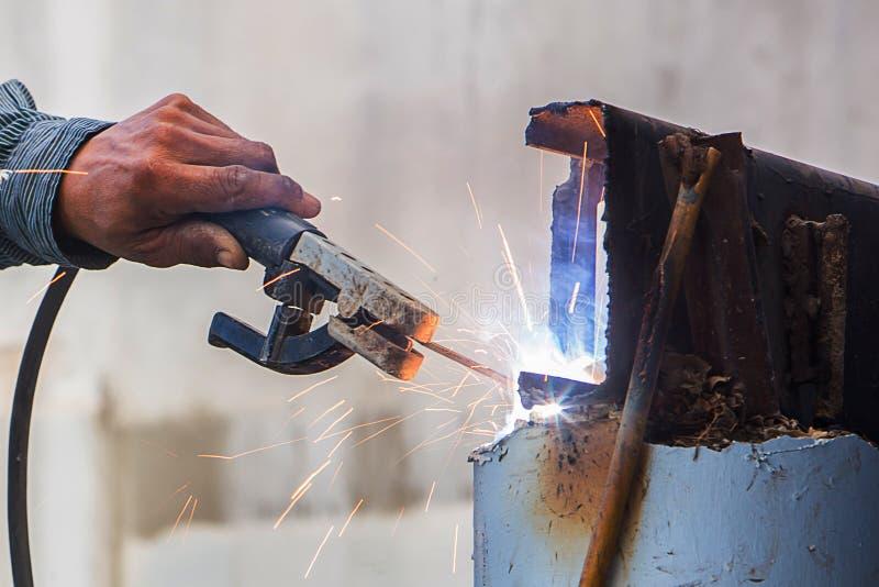 Fer de soudure de travailleur dans le chantier de construction photographie stock libre de droits