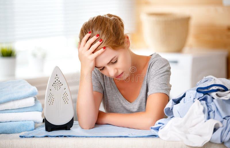 Fer repassant de vêtements de femme au foyer fatiguée de femme dans la blanchisserie photos stock