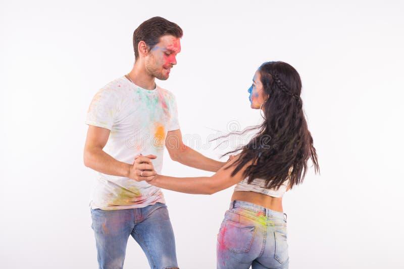 Feriado, conceito social da dan?a, do holi e dos povos - par feliz que tem o divertimento com p? colorido e que dan?a o bachata o imagens de stock