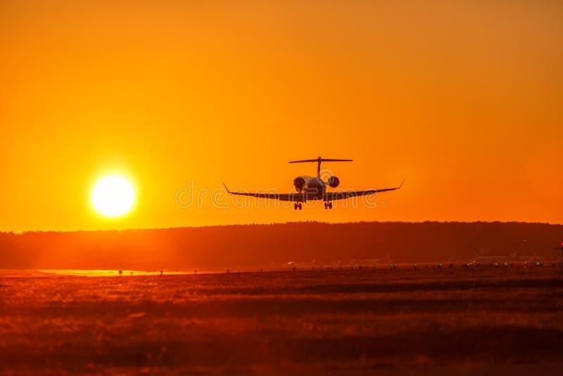 Feriado das férias do jato privado do por do sol do sol do aeroporto da aterrissagem de avião imagens de stock royalty free