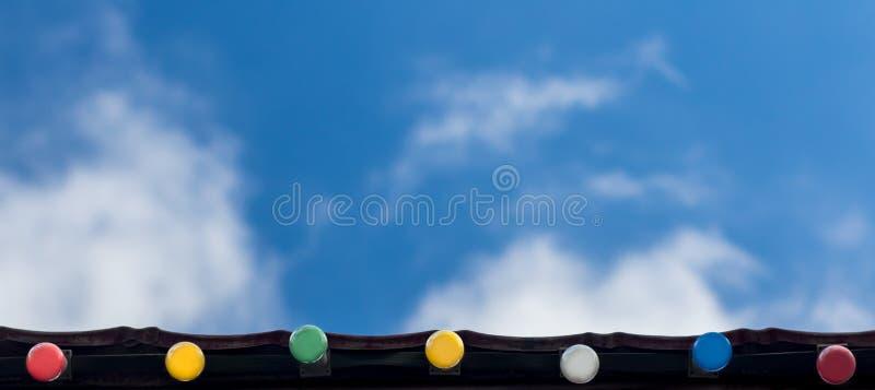 Feriado feliz, conceito do fundo da celebração do evento: linha de ampolas coloridas no beirado do telhado que olham acima, no cé foto de stock