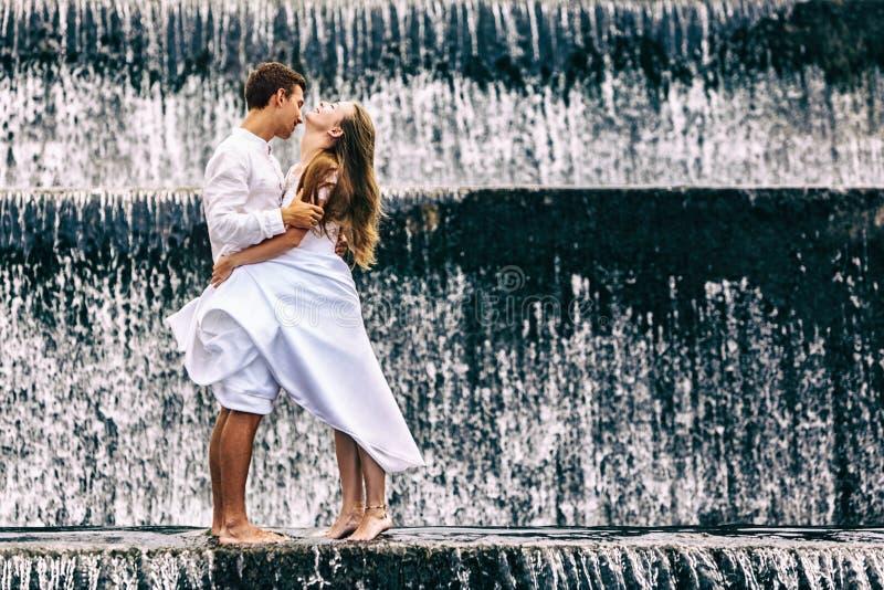 Feriado feliz da lua de mel da família Pares na associação da cachoeira da cascata fotografia de stock