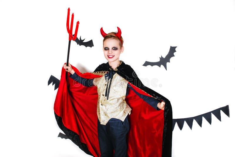 Feriado Halloween a criança engraçada no carnaval traja o diabo em um fundo branco imagens de stock