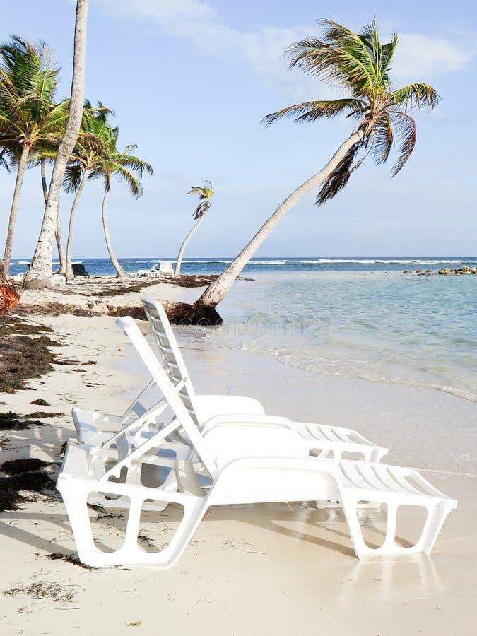Feriado tropical do Palm Beach com as cadeiras na areia branca com o céu azul nebuloso imagens de stock
