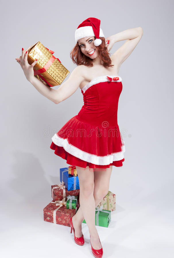 Feriados conceito e ideias Santa Helper Holding Golden Gift de cabelo vermelha caucasiano de sorriso feliz à disposição fotos de stock royalty free