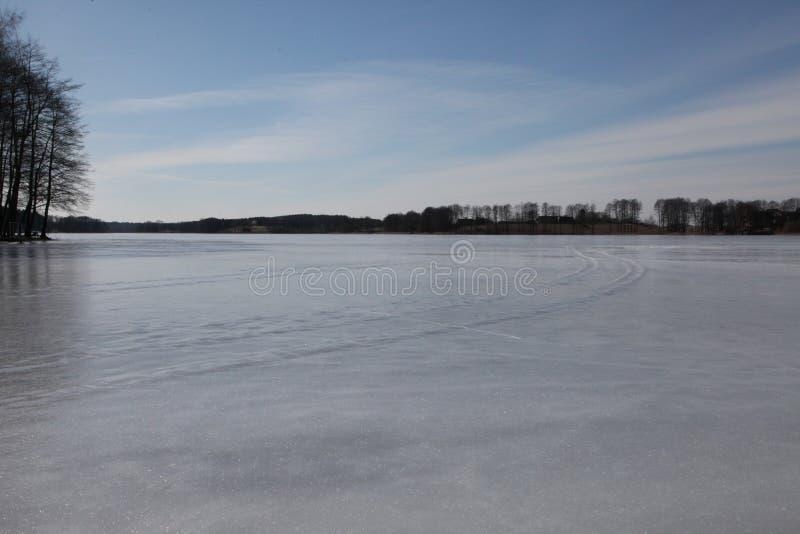 Feriados da mola Gelo congelado do lago, céu azul, árvores fotos de stock