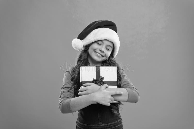 Feriados de inverno felizes Menina pequena Presente para o Xmas Inf?ncia Crian?a da menina no chap?u de Santa Compra do Natal, id fotos de stock