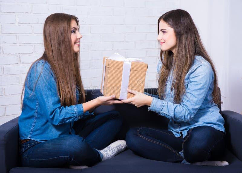 Feriados e conceito da amizade - meninas felizes com sitt da caixa de presente fotos de stock royalty free