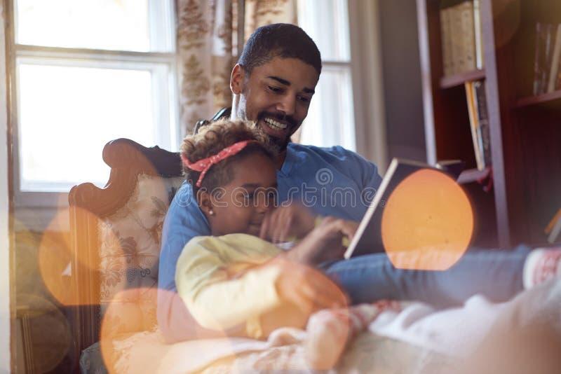 Feriados e conceito da celebração - tempo do Natal da despesa do pai e da filha junto, contos de fadas da leitura do paizinho fotos de stock