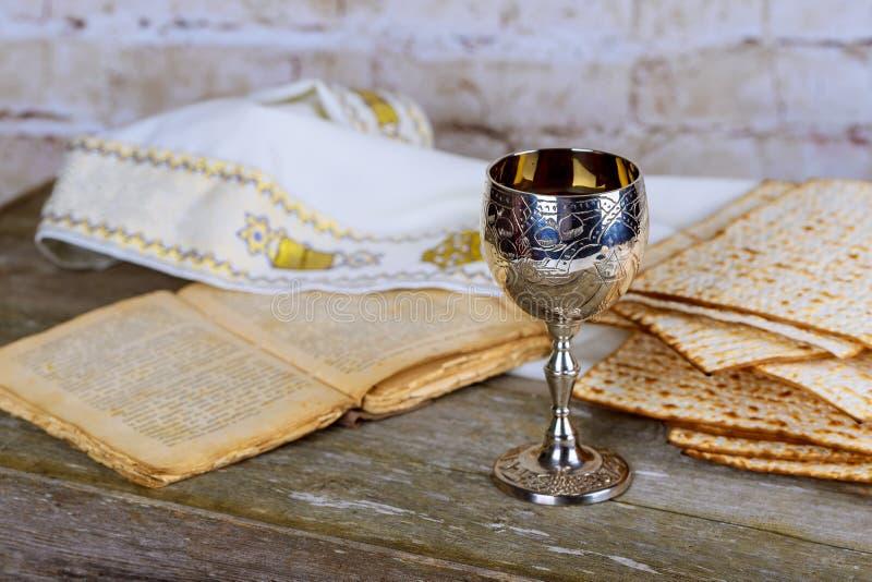 Feriados judaicos: Matzah de Pesach da páscoa judaica e um copo de prata completo do vinho com uma bênção tradicional imagens de stock