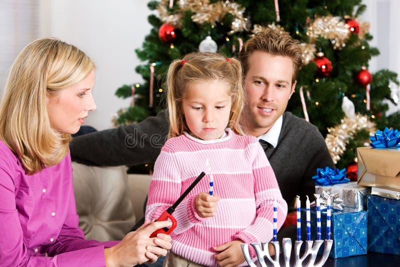 Feriados: Menina que ilumina velas para o Hanukkah fotografia de stock royalty free