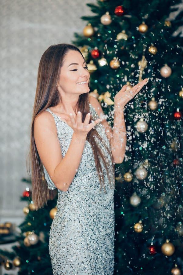 Ferie-, beröm- och folkbegrepp - ung kvinna i elegant klänning över julinrebakgrund Lycklig glad flicka arkivfoton