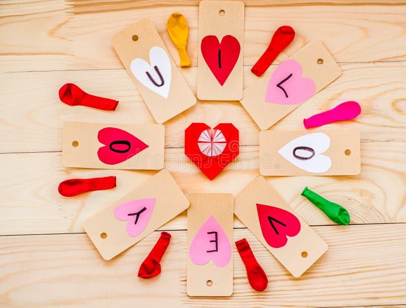 Ferie för dag för valentin` s hand - gjorda pappers- hjärtaetiketter på lantlig bakgrund i cirkel med färgrika ballonger och röd  arkivfoto