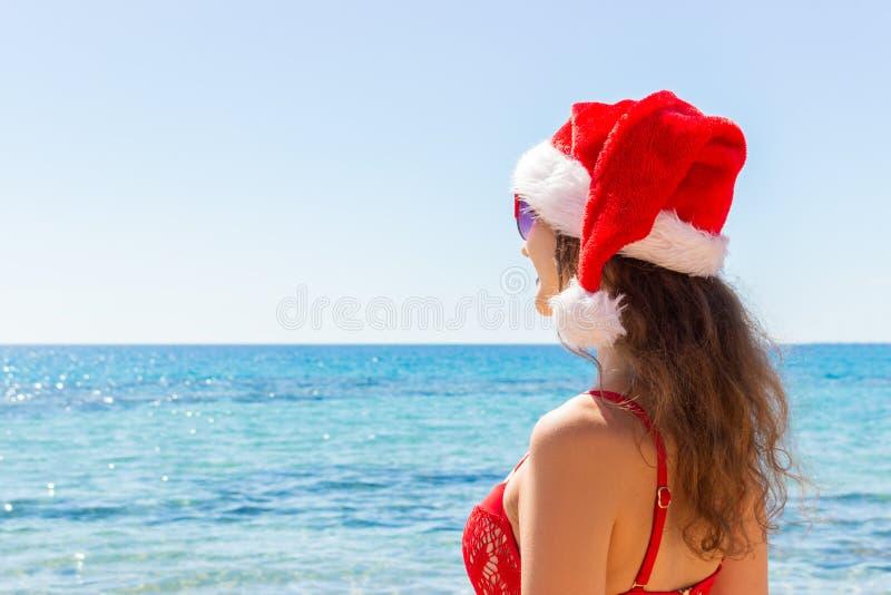 Ferie för julsemesterparadis sexig kvinnaglädje och framgång som tycker om solen, reser flykt med den santa hatten arkivbilder