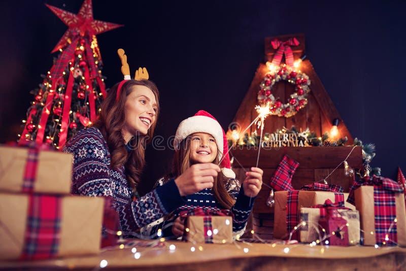 Ferie-, familj- och folkbegrepp Lycklig moder och liten flicka i santa hjälpredahatt med tomtebloss i händer, gåva royaltyfria foton