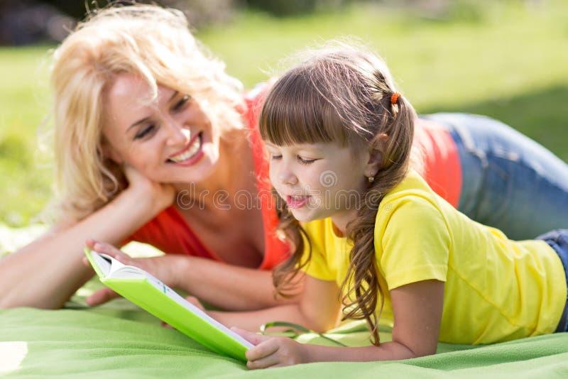 Ferie i natur Moder- och barndotter som har gyckel på gräsmattan arkivfoton