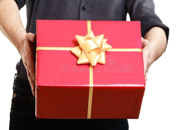 ferie Man att ge den röda gåvaasken med guld- ribbo royaltyfri bild
