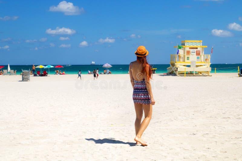 Ferie på Miami Beach Florida Tillbaka sikt av den röda hårkvinnan i den trendiga stilsommardräkten, livräddaretorn, spela för bar royaltyfria bilder