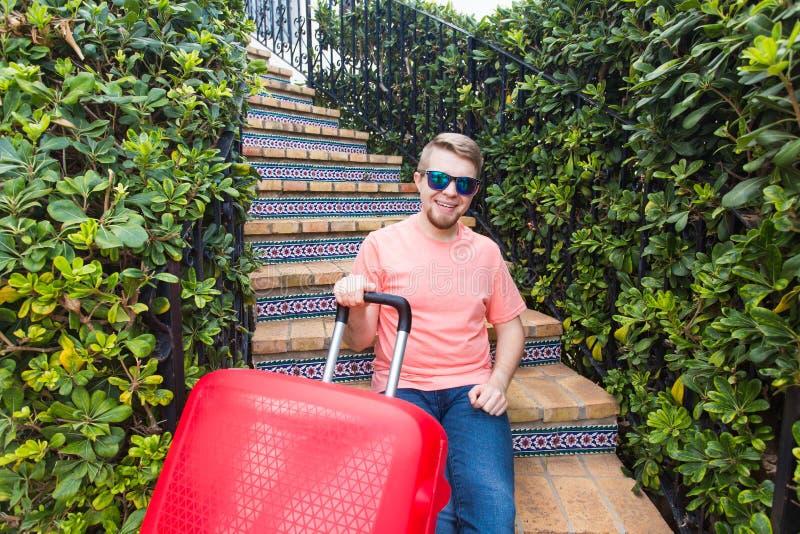 Ferie, resa och bagagebegrepp - ung man med resväskan som sitter på trappa royaltyfria foton