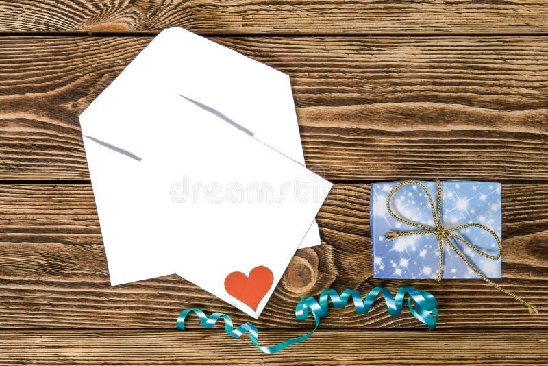 Ferie-/romantiker-/bröllop-/valentindagbakgrund med den lilla blåa handgjorda gåvaasken, kuvertet, meddelandekortet och bandet fotografering för bildbyråer