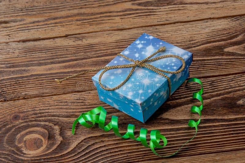 Ferie-/romantiker-/bröllop-/valentindagbakgrund med den lilla blåa handgjorda gåvaasken och bandet arkivfoton