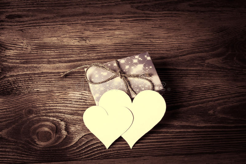 Ferie-/romantiker-/bröllop-/valentindagbakgrund med det tomma meddelandekortet i form av två hjärtor på trätabellen royaltyfri fotografi