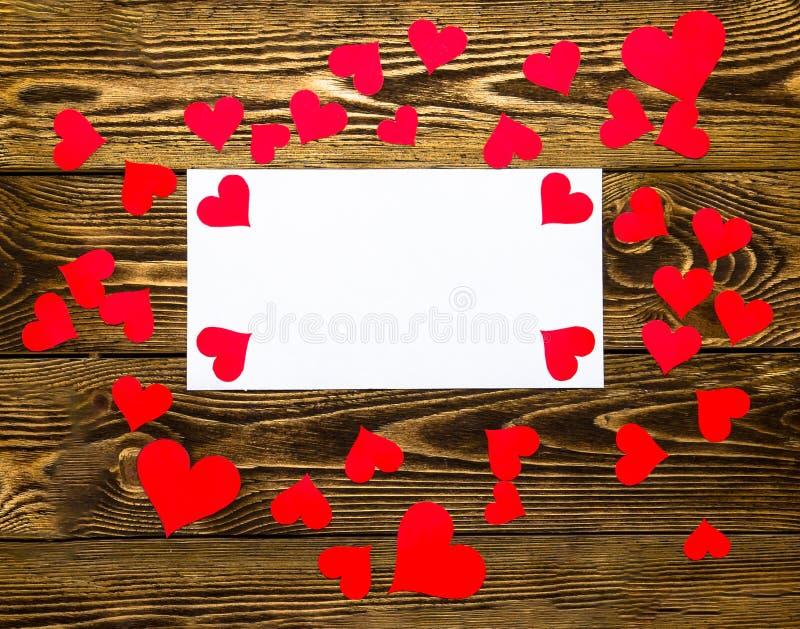 Ferie-/romantiker-/bröllop-/valentindagbakgrund med små pappers- röda hjärtor och det tomma meddelandekortet arkivfoto