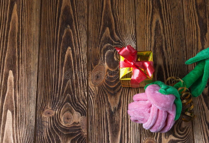 Ferie-/romantiker-/valentindagbakgrund med rosa plysch och gåvaasken på trätabellen arkivfoto