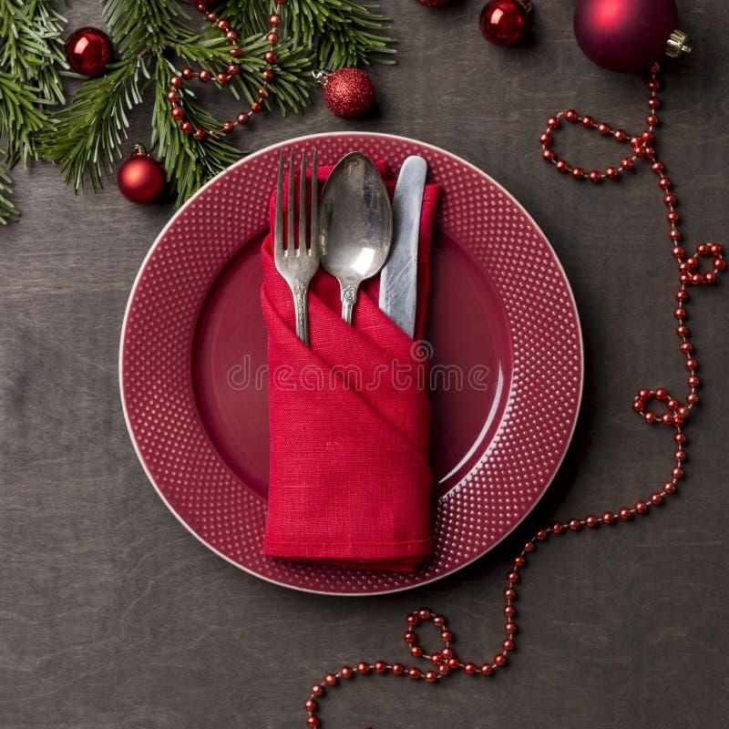 Ferie som tjänar som den röda plattan med gaffeln, skeden och kniven på träbakgrund royaltyfri foto