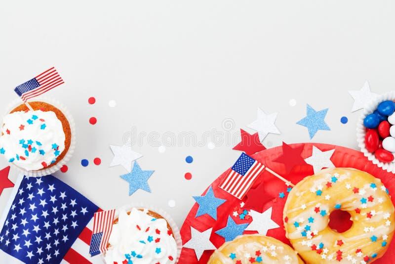 Ferie4th juli bakgrund med amerikanska flaggan dekorerade av söta foods, stjärnor och konfettier Lycklig självständighetsdagentab arkivbilder