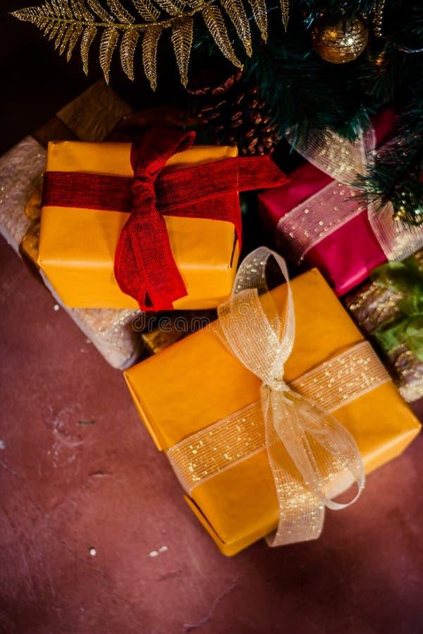 Feriegåvan under julgranen som slås in med tvinnar, och inpackningspapper som dekoreras med girlandljus och leksaker ferie royaltyfria bilder