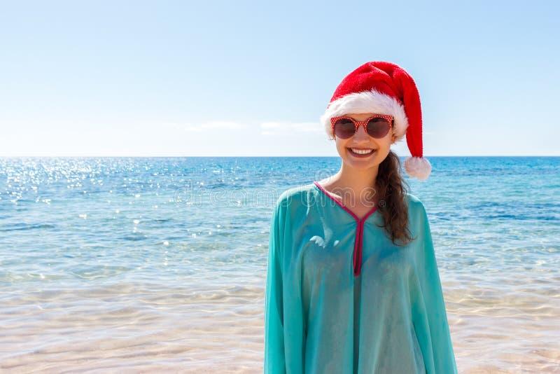 Feriekvinna i den santa hatten som kopplar av på paradisstranden julen förband den tomma speciellt bilden för kontoret för indust fotografering för bildbyråer
