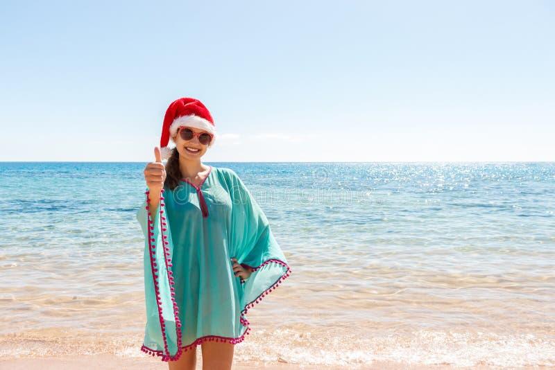Feriekvinna i den santa hatten som kopplar av på paradisstranden julen förband den tomma speciellt bilden för kontoret för indust arkivbilder