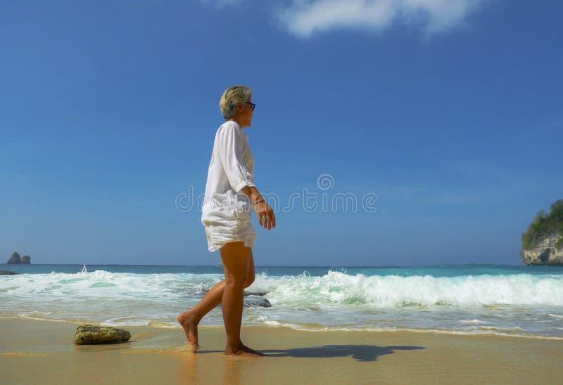Ferielivsstilstående av den lyckliga och avkopplade asiatiska mogna kvinnan på hennes 50-tal med grått hår som går på den tropisk royaltyfri foto