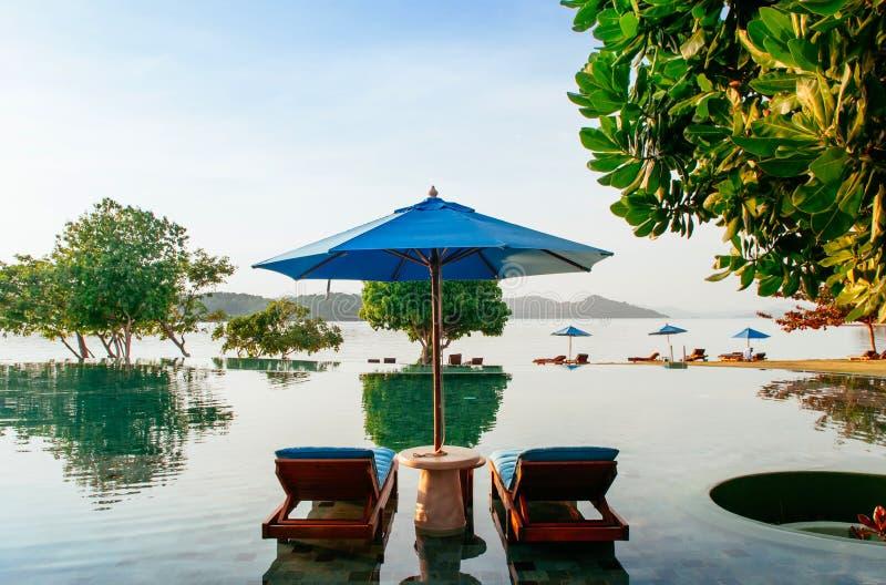 Ferien-Entspannungserholungsort-Strandbett in Unendlichkeitspool tropisches s stockbild